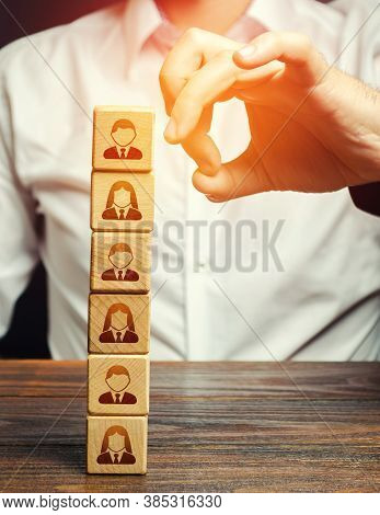 Man Knocks Down A Tower Of Blocks With Employees. Mass Layoffs, Closing A Business Company. Dismissa