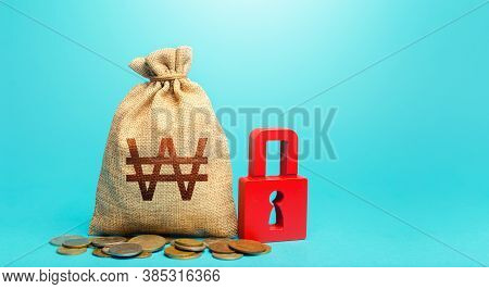 South Korean Won Money Bag And Red Padlock. Blocking Bank Accounts And Seizing Assets. Tight Governm