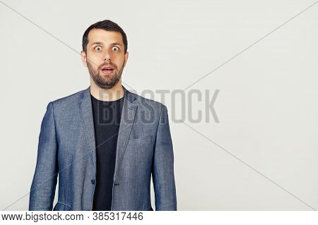 Male Businessman With A Beard In A Jacket, Afraid And Shocked By Unexpected Expression, Fear And Exc