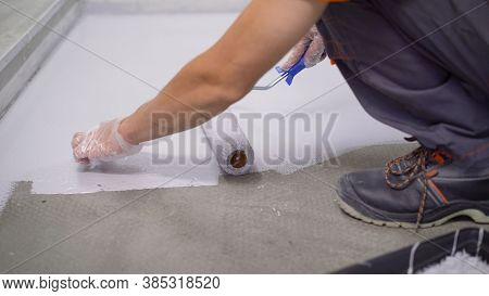 Contract Painter Painting Garage Floor To Speed Up Selling Of Home. Paint The Floor With A Roller.