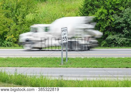 Horizontal Shot Of A Speeding Concrete Truck Streaking By A Speed Limit Sign.  Blurring Shows Motion