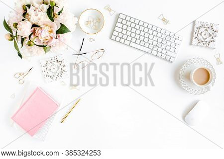Flat Lay Womens Office Desk. Female Workspace With Computer, Pink Peonies Bouquet, Accessories On Wh