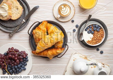 Beautiful Morning Breakfast With Fresh Croissants, Granola With Yoghurt And Berries, Toasts, Coffee