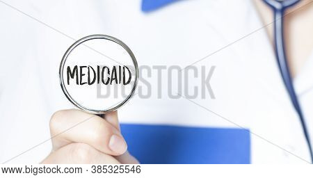 Doctor Holding A Stethoscope With Text Medicaid, Medical Concept