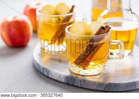 Apple cider cocktail with cinnamon and apple slices. Mulled apple wine for Christmas.
