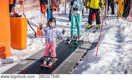 Young, Happy Skier Girl Going Up On Conveyor Lift Belt To Green Ski Zone For Ski Lessons, Bialka Tat