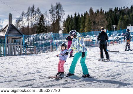 Young happy skier girl learning how to ski with her mom on the green ski zone, Bialka Tatrzanska, Tatry, Poland