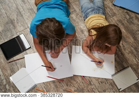 Siblings Playing Together At Home. Top View Of Little Boy And Girl Lying On The Wooden Floor And Dra