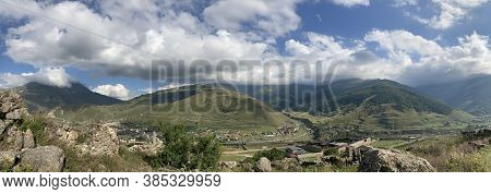 Mountain Peaks Against Cloudy Sky. Peaks Of Magnificent Rocks Located Against Bright Cloudy Sky