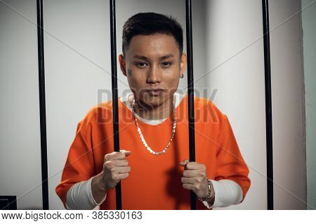 A Convicted Asian Man In An Orange Robe, With A Chain And Bracelet And A Tattoo On His Face Stands I