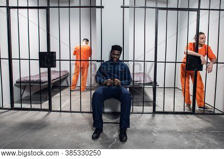 A Prison Warden Guards Cells And Surfs The Internet Via Smartphone With Dangerous Prisoners In Orang