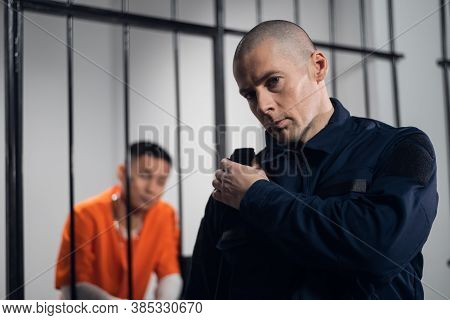 A Stern, Bald Prison Warden Makes The Rounds Of The Cells And Transmits Information Over The Radio T
