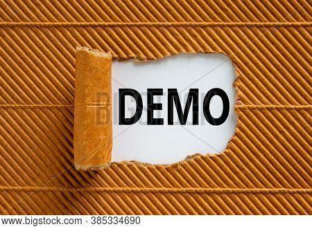 The Word 'demo' Appearing Behind Torn Brown Paper. Business Concept. Copy Space.