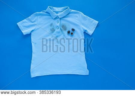 Dirty Stain Of Black Olives On A T-shirt, Isolated On A Blue Background