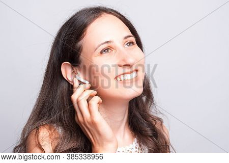 Close Up Portrait Of Charming Young Woman Using Earpods Over White Background