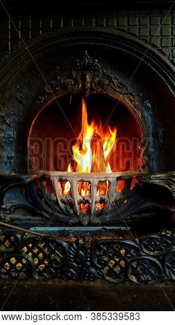 Fire Burning In Black Forged Vintage Fireplace. Concept Of Cozy Home