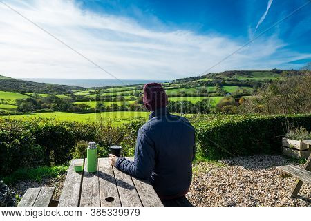 Backview Young Man In Warm Clothes Sitting In Farmer Wooden Cafe And Enjoying Local Nature View With