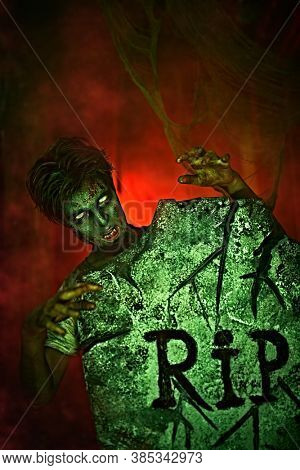 Horrible Halloween. Scary zombie boy teenager peeps out from behind the headstone in the cemetery. Copy space.