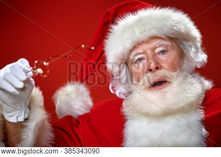 Close-up portrait of a jolly Santa Claus with glasses over festive red background. Merry Christmas and Happy New Year!