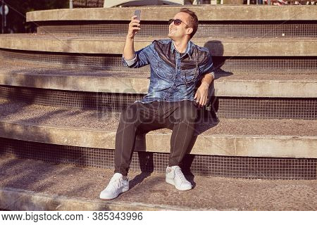 Smiling Man 27 Years Old Is Sitting On The Beton Stair And Taking Selfie During Walk Over The City.