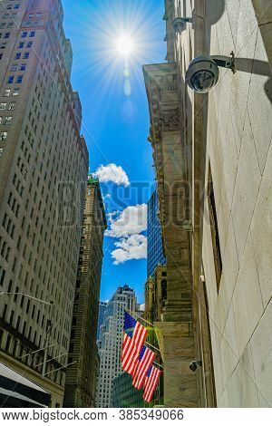 Wall Street, The Sun In The Sky Illuminates The 3 American Flags Attached To The Facade Of Building,