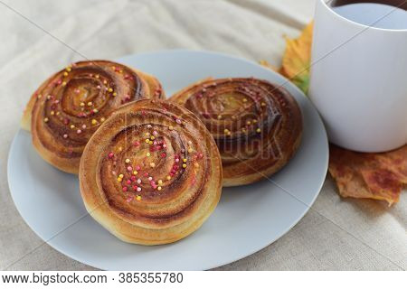Fresh Baked Cinnamon Rolls Or Buns With Sugar Sprinkle Topping On White Plate And Cup Of Black Tea O