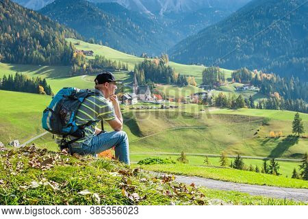 Man Tourist Looking At The Picturesque Village Of Santa Magdalena In Northern Italy On The Slopes Of
