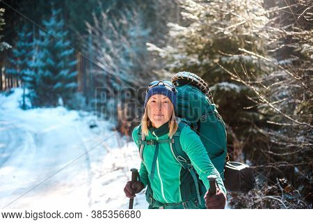 Woman With Backpack And Snowshoes In The Winter Mountains. Travel To Scenic Places. Portrait Of A Bl