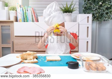 Cute Asian Boy Wearing Chef Hat And Apron Having Fun Preparing Sandwiches, Little Kid Making Cookie