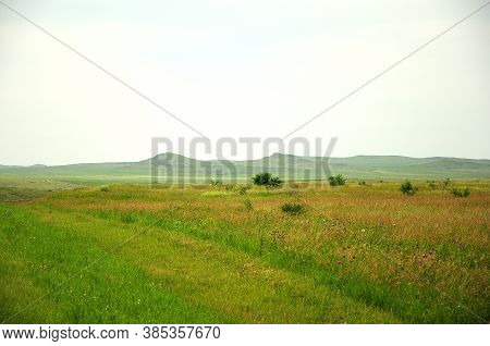 A Faint Road Leading Through A Field Overgrown With Grass At The Foot Of A High Hill.