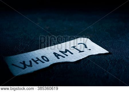 a piece of paper with the question who am I written in it, on a black textured surface