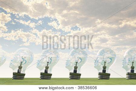 Row of human head light bulbs in landscape