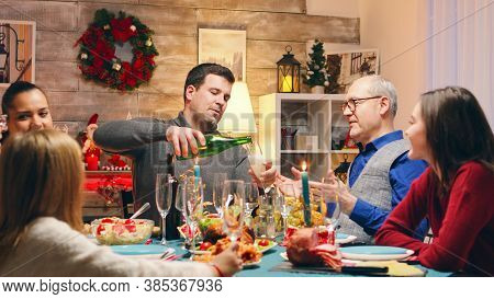 Adult Man Pouring Champagne For His Father At Christmas Family Reunion. Winter Holiday Gathering. Tr