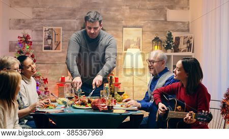 Girl Singing A Song On Guitar While Her Father Is Slicing The Chicken At Christmas Family Reunion. T