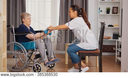 Nurse Helping Senior Woman In Wheelchair With Rehabilitation. Training, Sport, Recovery And Lifting,