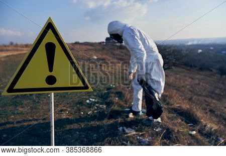 Warning Sign About Danger And Hazards. On Blurred Background Environmentalist In Protective Suit And