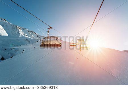 Ski Lift Empty Ropeway On Hilghland Alpine Mountain Winter Resort On Bright Sunny Evening . Ski Chai