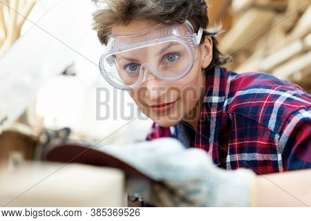 Young Professional Beautiful 30-40 Female Carpenter Looking And Sanding Raw Wood With Sandpaper In C