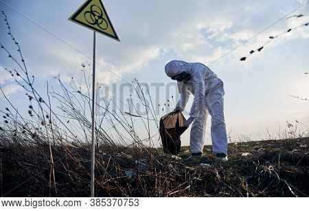 Ecologist Wearing White Protective Coverall, Gas Mask, Collecting Plastic Garbage Into Black Waste B