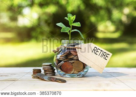 Retire. Glass Jar With Coins And A Plant In It, With A Label On The Jar And A Few Coins On A Wooden