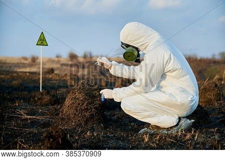 Side View Snapshot Of Crouched Researcher Wearing A White Coverall, Gas Mask And Gloves Collecting S
