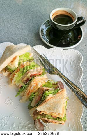 Plate Of Delectable Sandwiches Served With A Cup Of Hot Coffee On A Marble Table