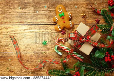 Christmas background with gift box, gingerbread cookies, branches of holly and fir on wooden background. Winter festive concept. Flat lay, copy space.