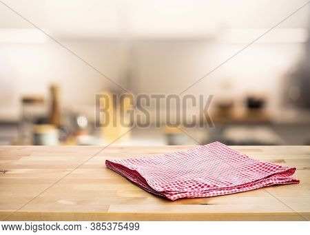 Red Fabric,cloth On Wood Table Top On Blur Kitchen Counter (room)background.for Montage Product Disp