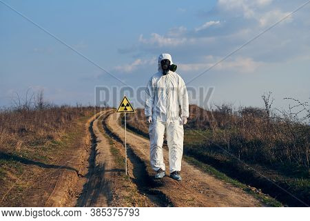Ecologist In White Coverall, Gas Mask And Gloves Standing On Village Road In The Field Next To Radia