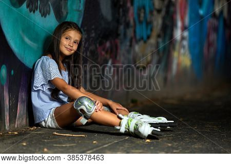Happy Tired Little Child Girl In Roller Skates Is Sitting After Rollerskating In Park In The Evening