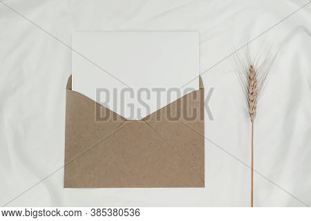 Blank White Paper Is Placed On The Open Brown Paper Envelope With Barley Dry Flower On White Cloth.
