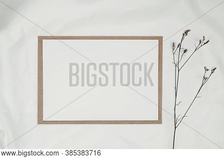 Blank White Paper On Brown Paper Envelope With Limonium Dry Flower On White Cloth. Mock-up Of Horizo
