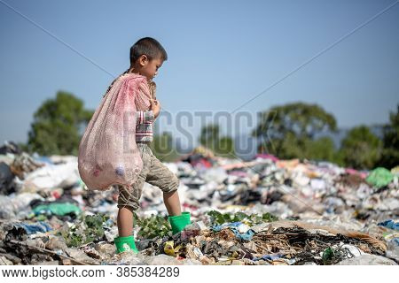 A Poor Boy Collecting Garbage Waste From A Landfill Site. Concept Of Livelihood Of Poor Children.chi