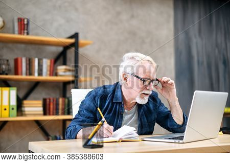 Focused Older Man In Smart Casual Wear Is Using Laptop Computer For Watching Online Classes And Webi